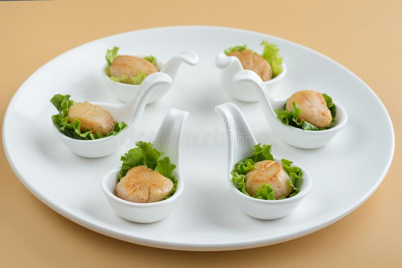 Scallop snack on spoon royalty free stock photography