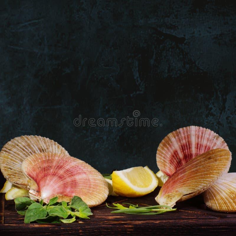 Scallops в раковинах, перед варить ингредиенты лежат на доске, рядом с лимоном и зелеными цветами стоковое изображение rf