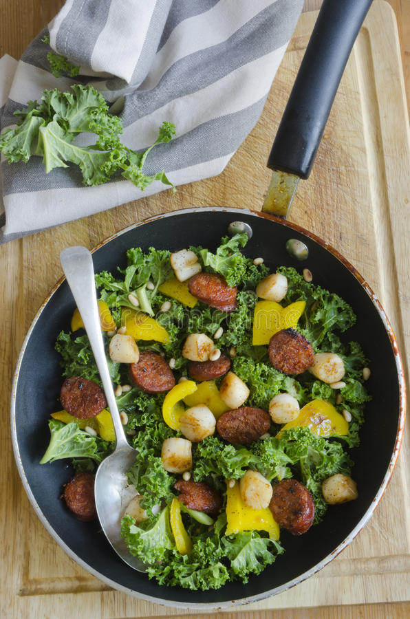 Scallops, chorizo and kale. Spanish sausage, scallops, kale and yellow peppers on a pan royalty free stock photography
