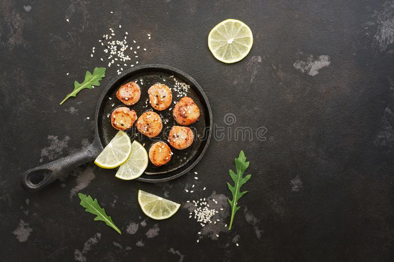 Scallops fried in a pan with lemon, on a black stone background. Top view, copy space royalty free stock photos