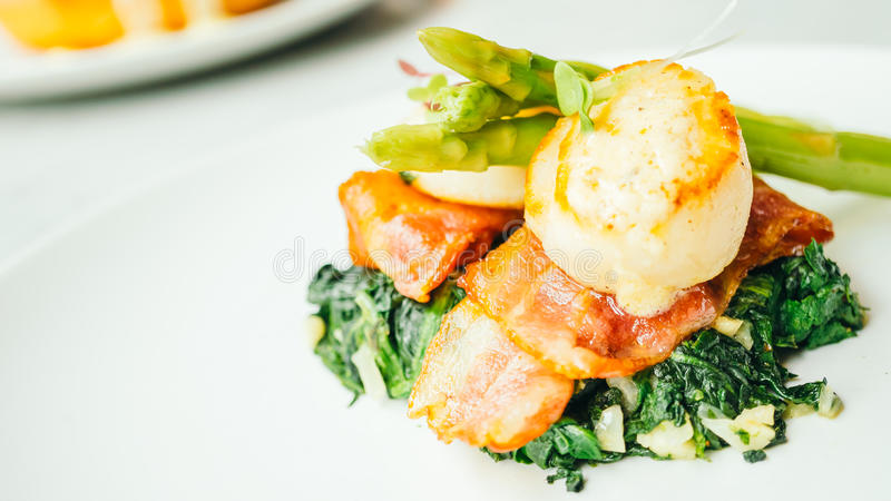 Scallops shell with bacon and asparagus stock photo