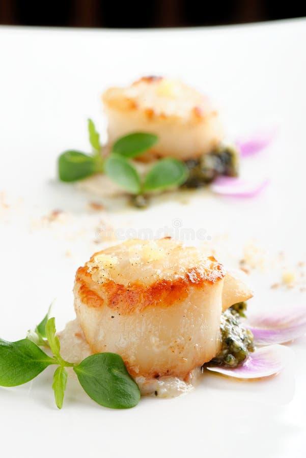 Scallops shells with thai basil pesto. On the plate stock image