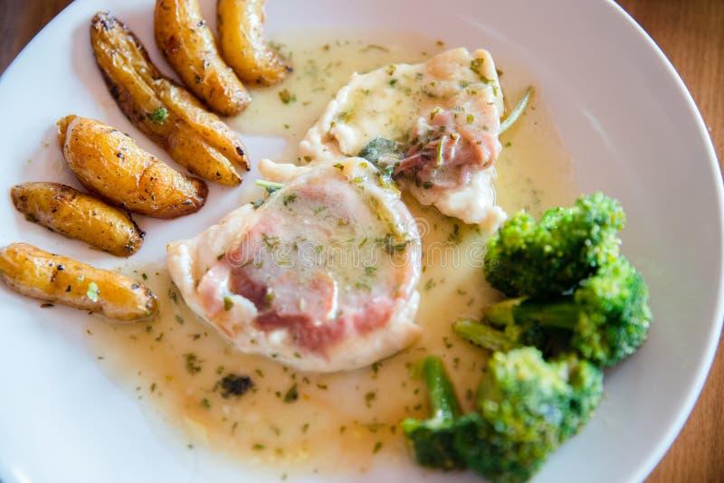 Scaloppina met rozemarijn met aardappelen in de schil op complexe achtergrond en broccoli stock foto's