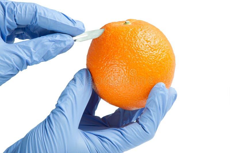 Scalpel en sinaasappel royalty-vrije stock afbeeldingen