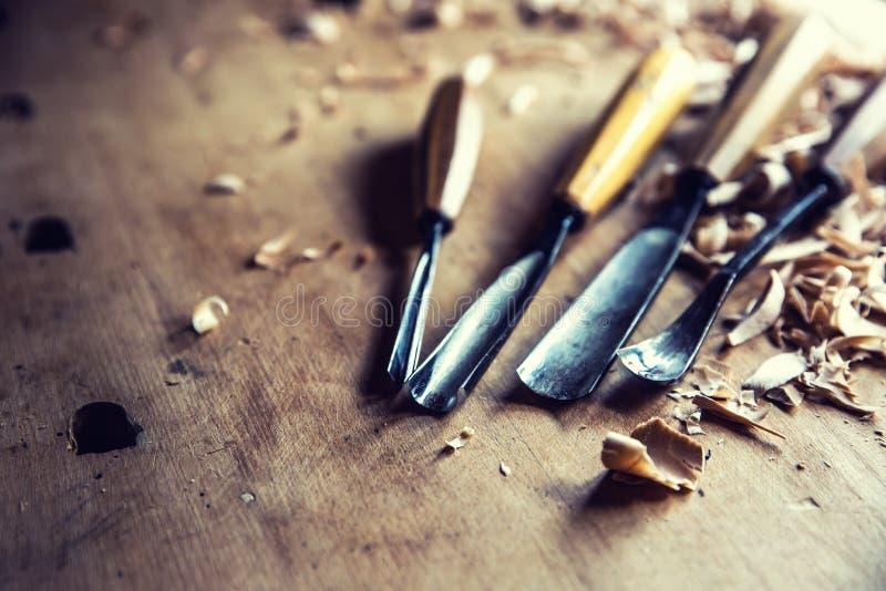 Scalpelli d'annata degli strumenti di falegnameria con gli shawings di legno sul retro banco da lavoro fotografia stock libera da diritti