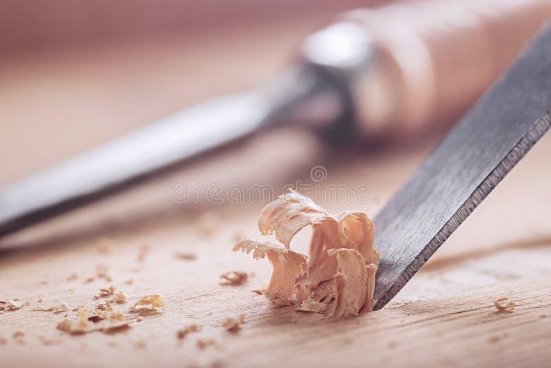 Scalpello da legno che taglia scanalatura nella vecchia plancia del pino per la serratura di porta fotografia stock