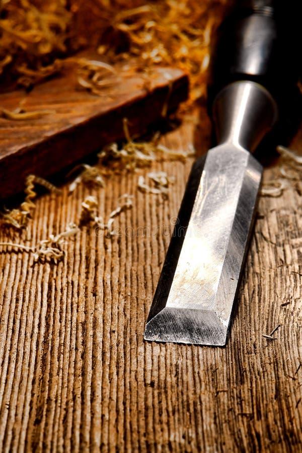 Scalpello da legno sulla vecchia stazione di lavoro di legno afflitta della scheda immagine stock