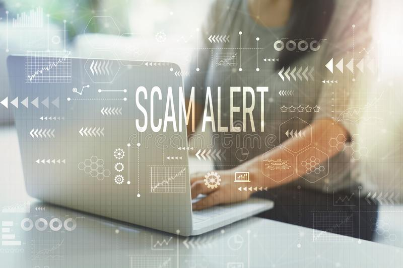 Scam alert with woman using laptop royalty free stock photo
