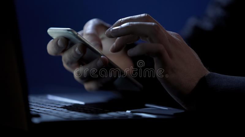 Scammer holds smartphone, cracks two-factor authentication, steals money online royalty free stock photos