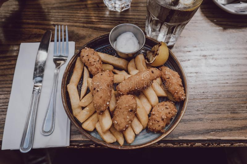 Scampi and chips popular British pub food, on a plate, on a wooden table stock images