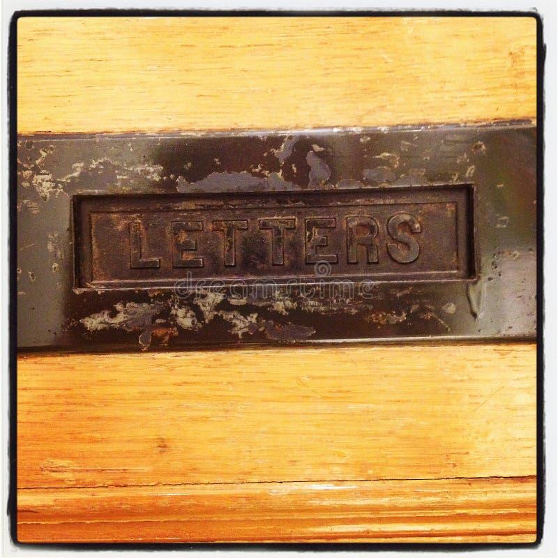 Scanalatura di posta in vecchia porta di legno immagine stock