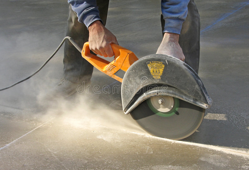 Scanalatura di taglio dell'uomo in lastra di cemento armato fotografia stock libera da diritti