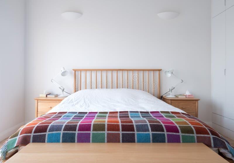 Scandi-Artschlafzimmer Innen mit hölzernen Schlafzimmermöbeln, weißen gemalten Wänden, weißer Bettwäsche und bunter Decke lizenzfreie stockfotos
