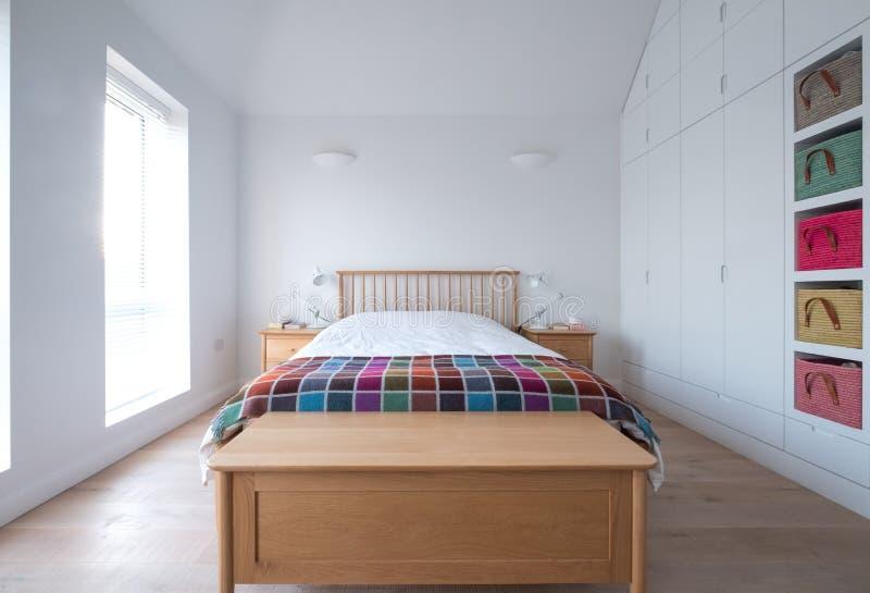 Scandi-Artschlafzimmer Innen mit hölzernen Schlafzimmermöbeln, weißen gemalten Wänden, weißer Bettwäsche und bunter Decke stockfotografie