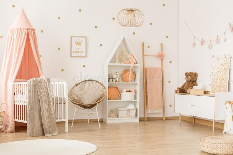 Scandi child`s bedroom interior. Teddy bear on white cupboard in scandi child`s bedroom interior with canopied crib stock photos