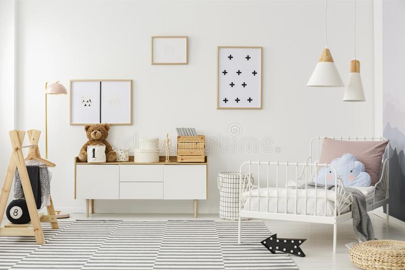 Scandi kid`s bedroom interior. Blue pillow on white bed in scandi kid`s bedroom interior with mockup of empty poster stock images