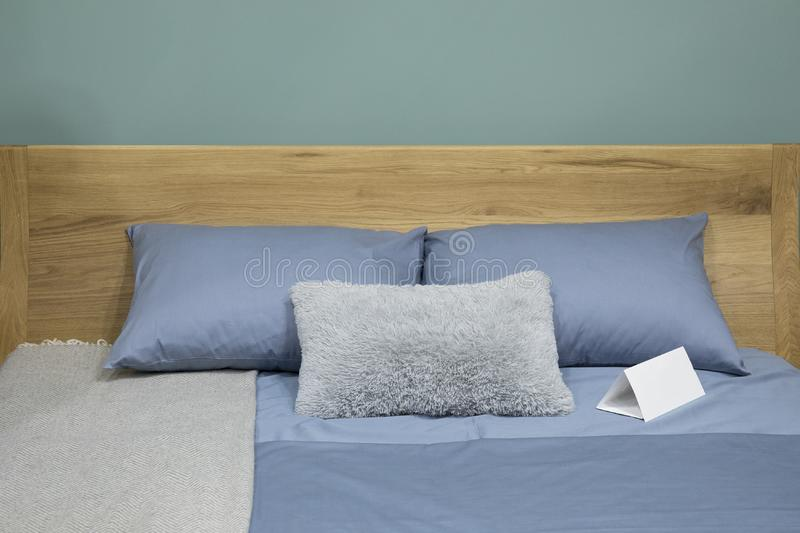 Scandinavian bedroom interior with with wooden bed and cozy blue pillows royalty free stock photography