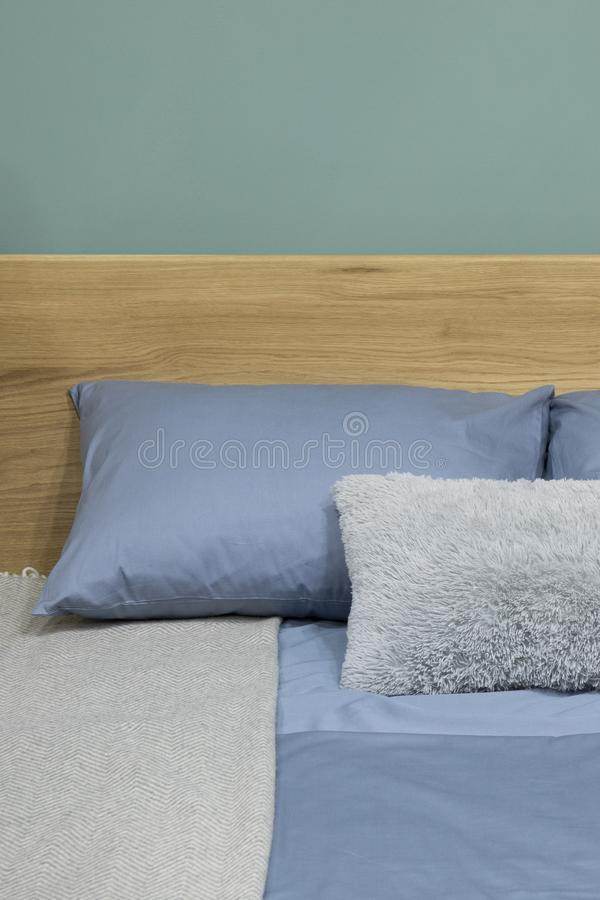 Scandinavian bedroom interior with with wooden bed and cozy blue pillows royalty free stock images