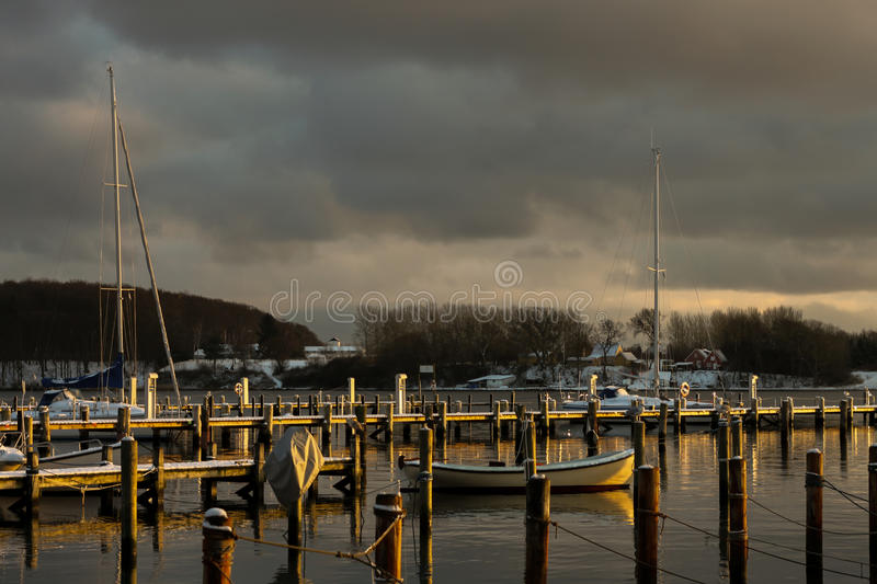 Scandinavian boats during sunset in winter royalty free stock photos