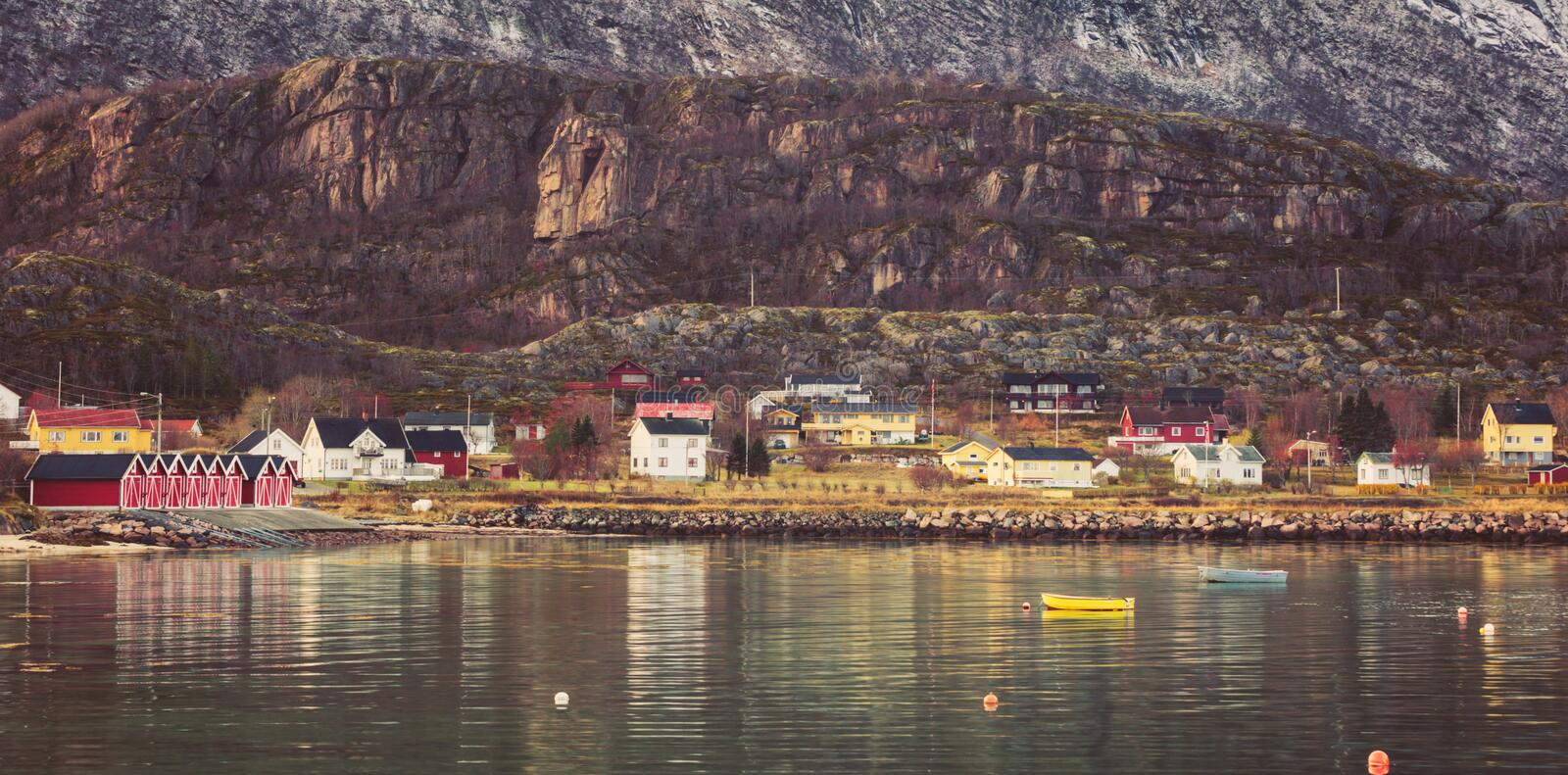 Scandinavian fishing village at the foot of the mountain. stock photos