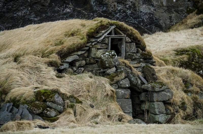 Old stone house destroyed ancient Viking overgrown with yellow dry grass in Iceland stock photography