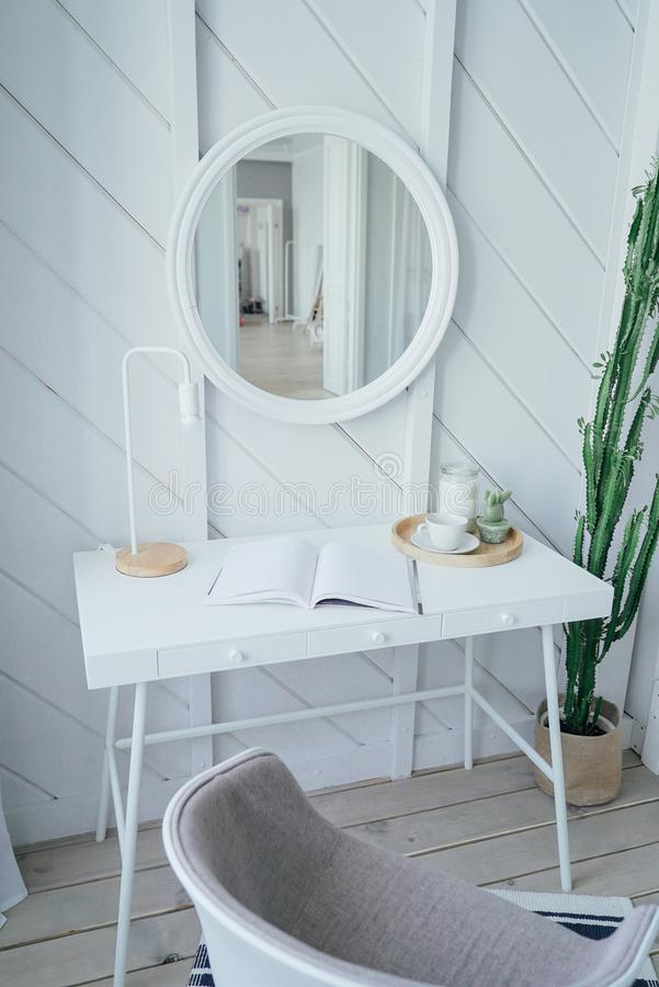 Scandinavian modern cozy eco interior, white table and mirror in bed room, minimalism stock photo