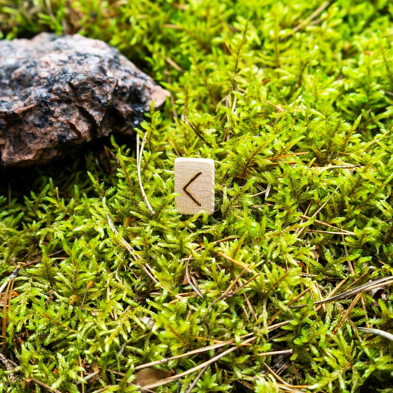Scandinavian rune Kano fire, beginning, on wet moss. The concept of predicting the future, an ancient way of divination royalty free stock photos