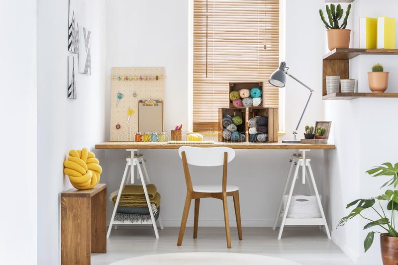 Scandinavian style hobby room interior with workspace for knitting, sewing, crocheting and designing handmade home textiles. Real stock photos