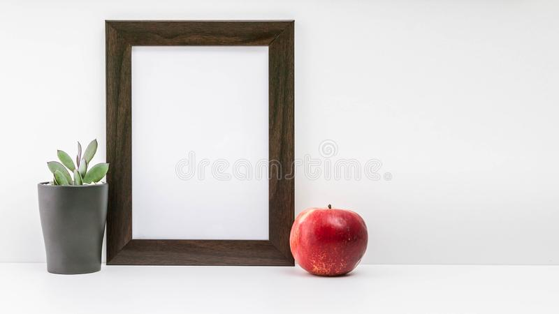 Empty dark photo frame, succulent in a dark pot and a red juicy apple on a white background. Scandinavian style in the interior. Scandinavian style in the stock images