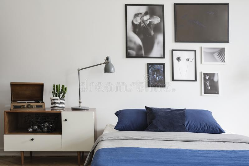 Scandinavian style, wooden dresser by a navy blue bed and framed art gallery on a white wall of a creative bedroom. Interior stock images