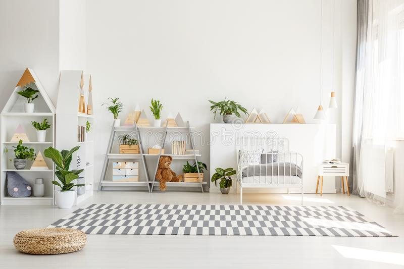 Scandinavian style, wooden furniture with plants and mountain decorations in a sunny, monochromatic child bedroom interior with wh royalty free stock photography