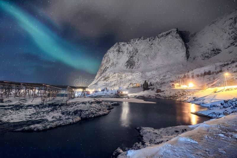 Scandinavian village illumination with northern lights shining on snow mountain royalty free stock photography