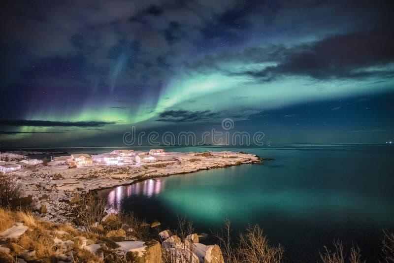 Scandinavian village illumination with northern lights on snow cape stock photos