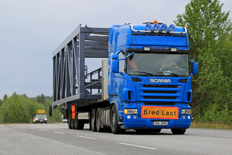 Scania Semi Truck Hauls a Wide Load. KONGINKANGAS, FINLAND - JUNE 20, 2015: Scania truck hauls a wide load accompanied by an escort car. The abnormal transport stock photo