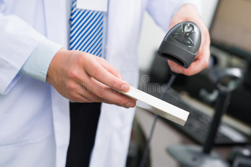 Scanning bar code. Cropped image of a pharmacist scanning bar code on the foreground stock photos