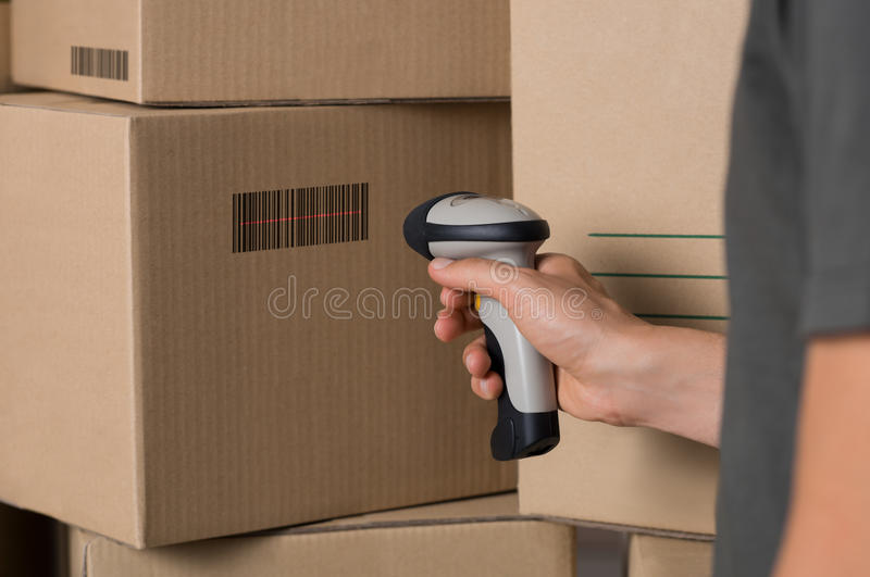 Scanning barcode on box. Courier scanning cardboard box with barcode scanner in warehouse. Close up of warehouse manager hand scanning boxes with barcode reader stock photos