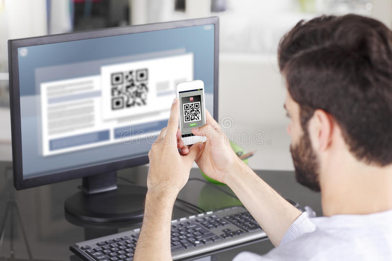 Scanning QR Code. Portrait of young businessman sitting at his workplace in front of computer monitor and scanning QR code with mobile smart phone royalty free stock photos