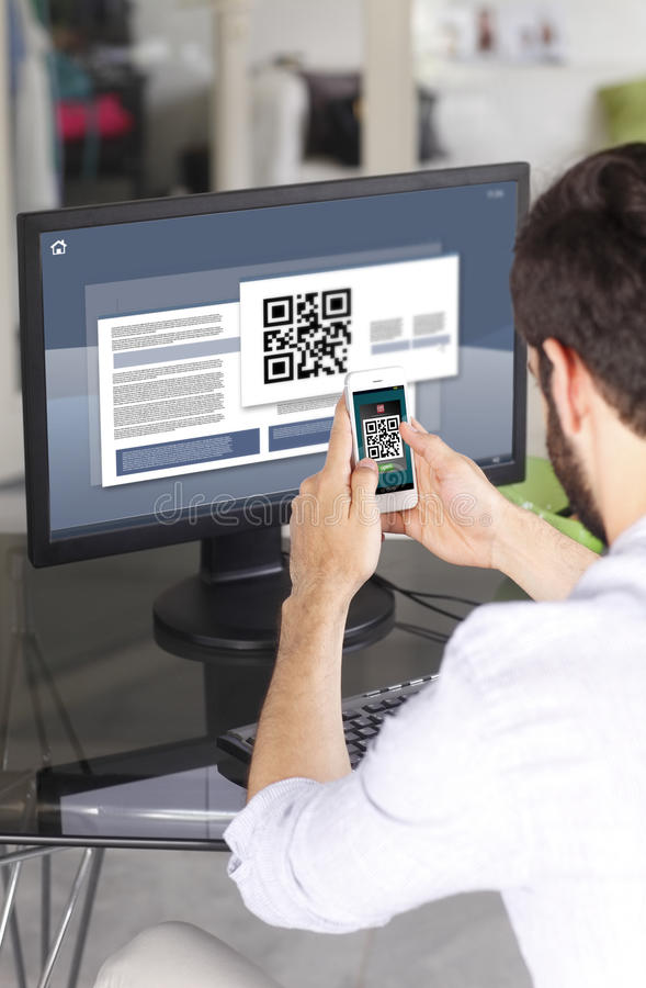 Scanning QR code. Portrait of young businessman sitting at his workplace in front of computer monitor and scanning QR code with mobile smart phone stock photo
