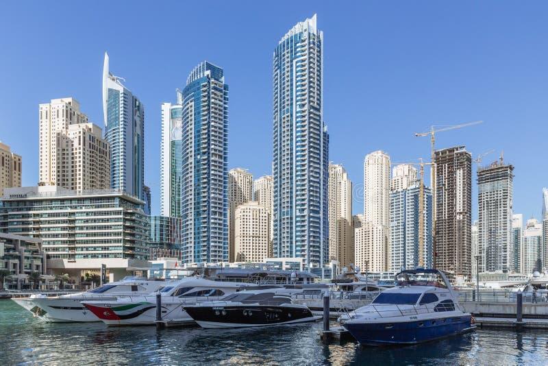Scape с современными многоэтажными зданиями, человек города сделало реку с яхтами и голубым небом в предпосылке на Дубай стоковое фото rf