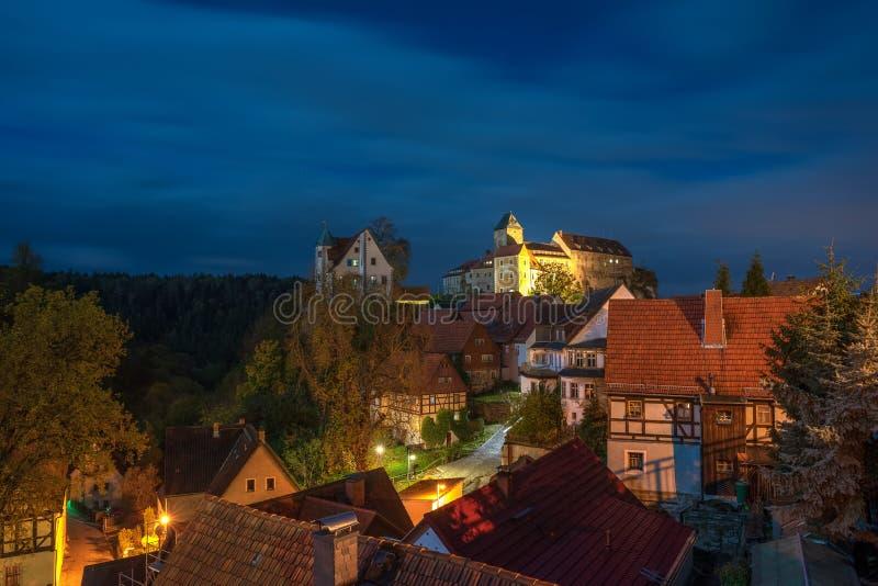 Scape cênico da noite da cidade de Hohnstein com castelo de Hohnstein e de casas de moldação puras da madeira em Suíça saxão, Ale foto de stock