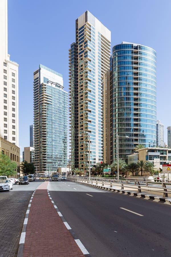 Scape da cidade com prédios modernos, estrada e o céu azul no fundo em Dubai foto de stock