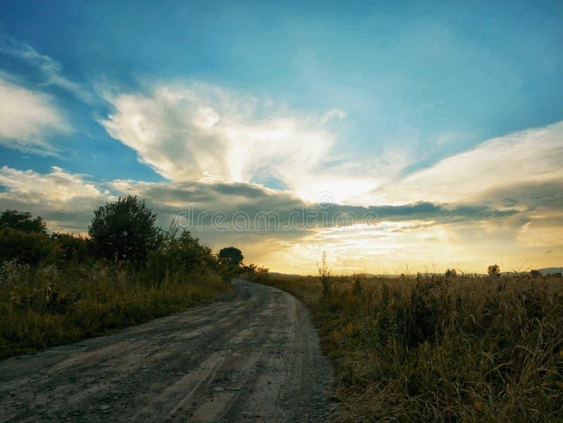 Scape de la tierra del camino polvoriento en el uso hermoso del cielo de la puesta del sol de la escena rural para el fondo natur imágenes de archivo libres de regalías