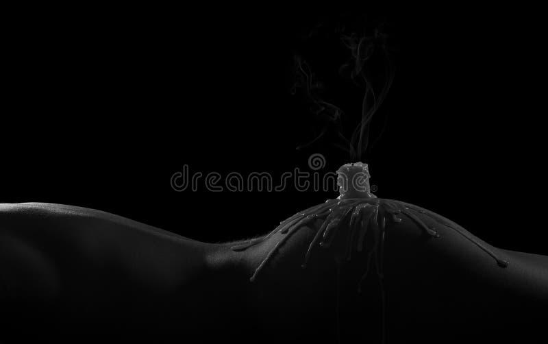 Scape del corpo della donna con la candela di fumo e sulla sua natica fotografia stock
