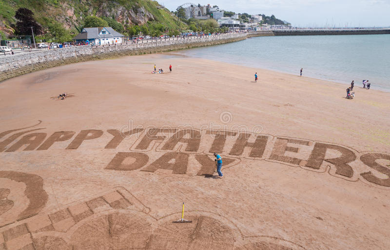 Scarborough beach, United Kingdom. Scarborough, United Kingdom June 21, 2015: Man writing father's day message in the sand on Scarborough Beach while families stock photo