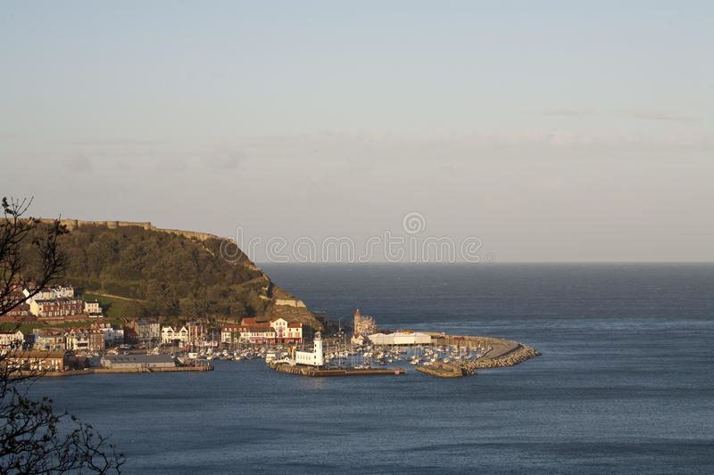 Scarborough, United Kingdom. A high vantage point view over the harbour at Scarborough on the North Sea. On the top of the cliffs is the wall of the 11th royalty free stock photography