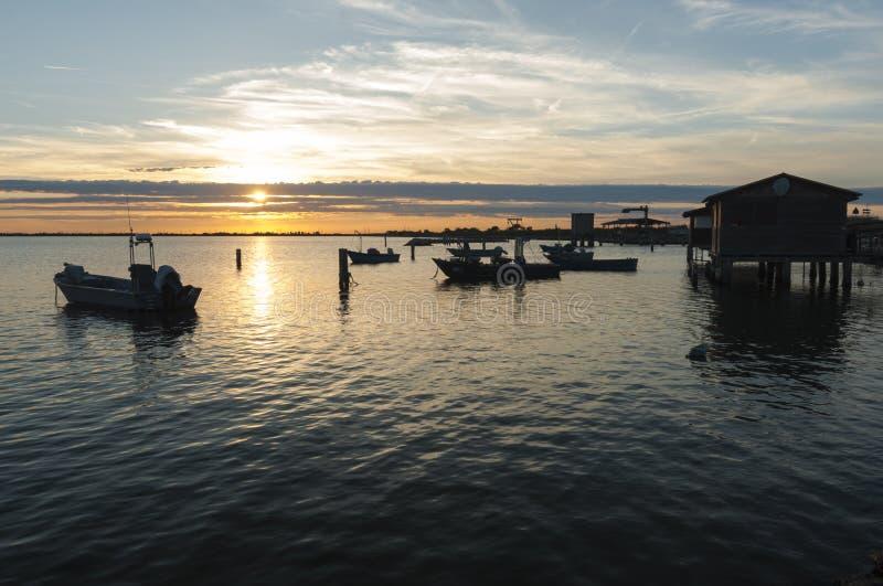 SCARDOVARI, ИТАЛИЯ, 2016-08-06: Хаты рыбной ловли на лагуне Scardovari стоковое фото