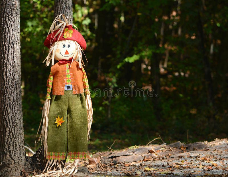Scarecrow leaning against tree stock images