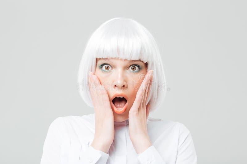 Scared冲击了有张的嘴的在面颊的妇女和手 免版税库存照片