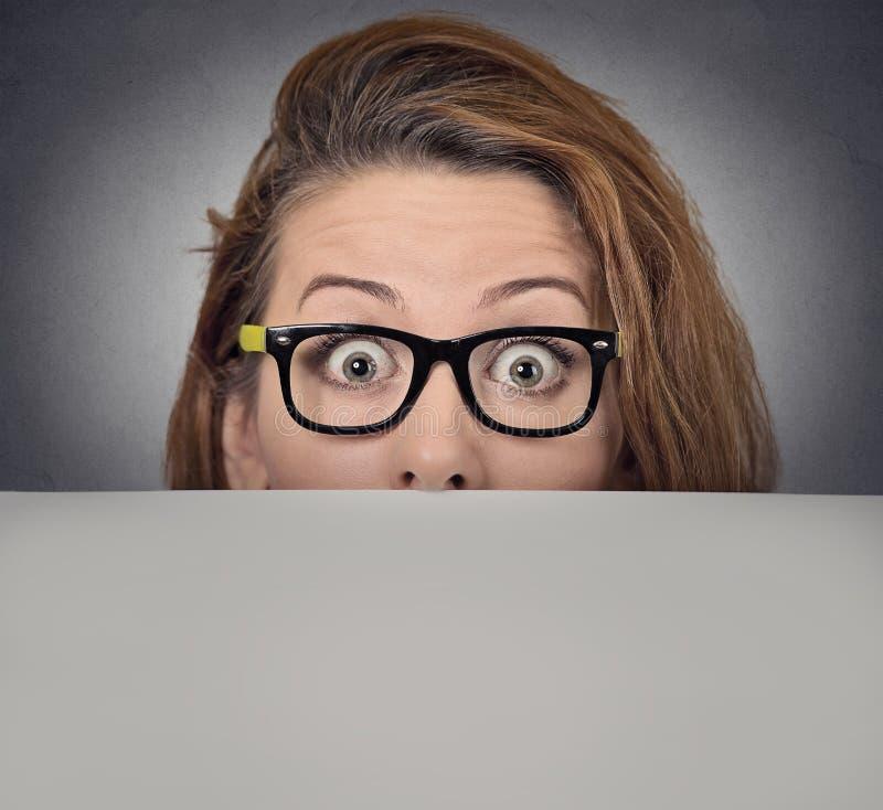 Scared a étonné la femme jetant un coup d'oeil au-dessus du bord du panneau d'affichage vide photos stock