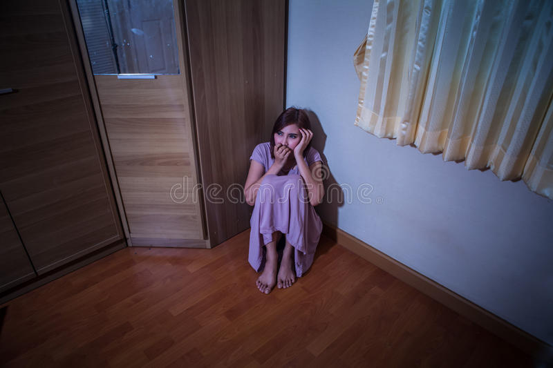 Scared abused woman sitting in the corner royalty free stock photos